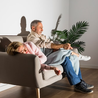 Aged woman and man with tv remote watching tv on sofa
