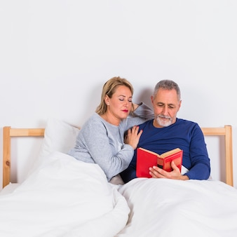 Aged woman near man with book in duvet on bed