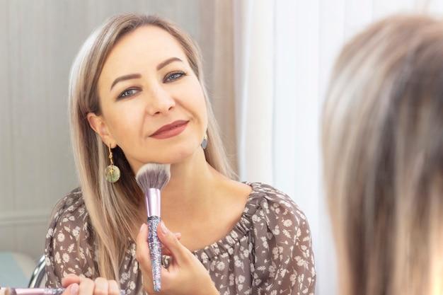 나이 든 여자는 그녀의 화장을한다. 거울을보고 있습니다. 나 자신에게 메이크업 아티스트. 큰 브러시로 얼굴에 파우더를 바르십시오.