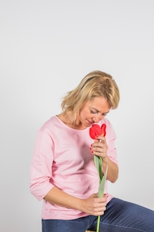 Aged woman in rose blouse smelling flower
