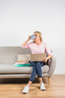 Aged woman in rose blouse with laptop and heap of books drinking from cup on sofa