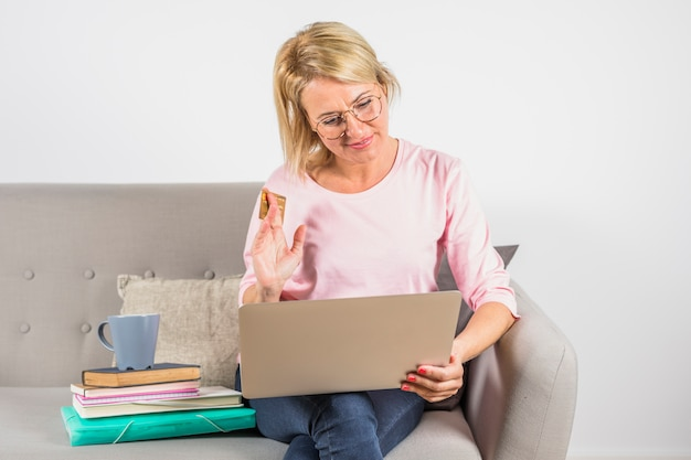 Aged woman in rose blouse with plastic card, laptop and cup on heap of books on sofa