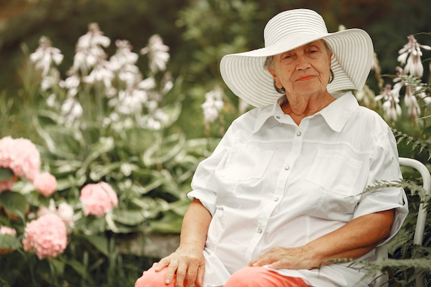 Пожилая женщина, сидящая в парке. бабушка в белой шляпе.
