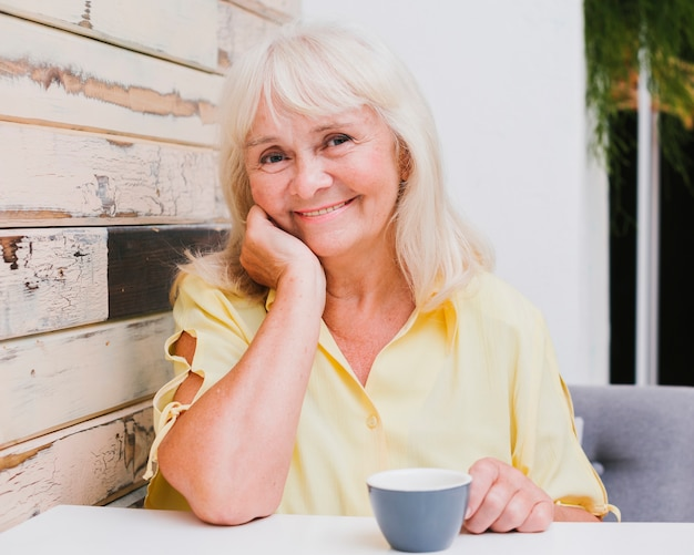 Aged woman sitting in kitchen with cup smiling