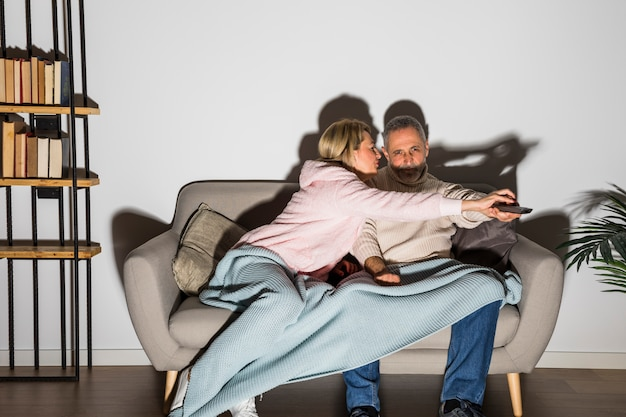 Aged woman stopping man with tv remote to change channel on tv on sofa
