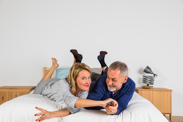 Aged woman stopping smiling man with tv remote to change channel on tv on bed