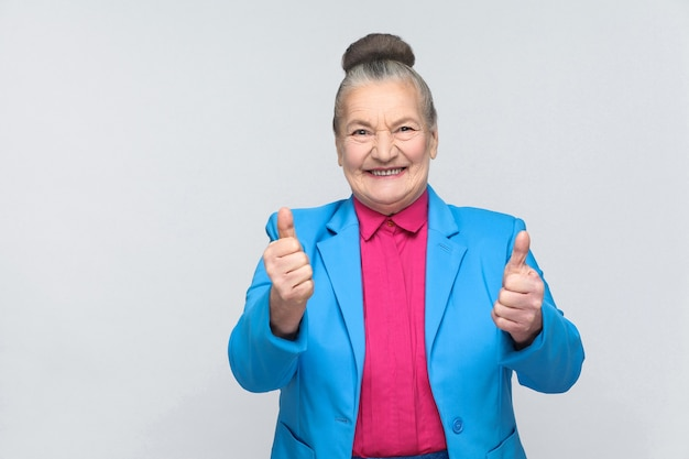 Aged woman toothy smiling and showing like sign