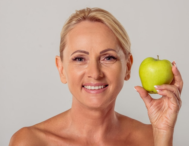 Aged woman with bare shoulders holding an apple.