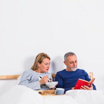 Aged woman with bowl near man with book in duvet near breakfast on tray on bed