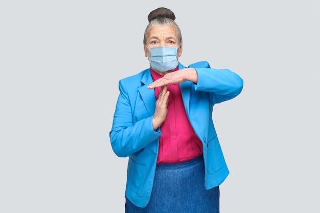 タイムアウトの兆候を示す外科用医療マスクを持つ高齢の女性。水色のスーツとピンクのシャツを着た祖母が、パンの灰色の髪を集めて立っています。灰色の背景で分離された屋内スタジオショット