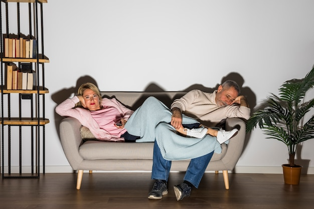 Aged woman with tv remote and man watching tv on sofa