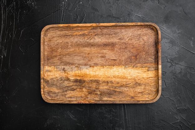Набор состаренной деревянной разделочной доски, плоская планировка, вид сверху, с местом для текста или вашего продукта, на черном фоне темного каменного стола