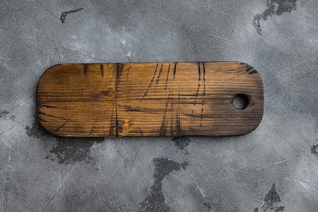 Набор состаренной деревянной разделочной доски, плоская планировка, вид сверху, с местом для текста или вашего продукта, на фоне серого каменного стола