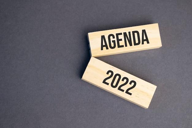 黄色の背景に木製のブロックの議題2022の言葉。ビジネス倫理の概念。