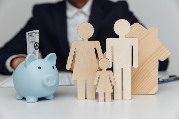 Агент, стоящий за фигурами молодой семьи и концепции покупки копилки или ипотеки