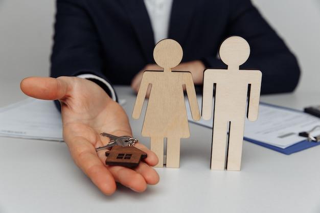 Агент дает ключ от дома к домовладению молодой паре