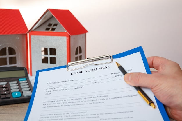 The agent holds the form of the real estate lease, house models, calculator.