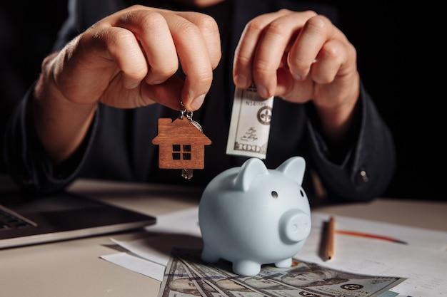Агент с ключами от дома и синей копилкой с долларовыми банкнотами