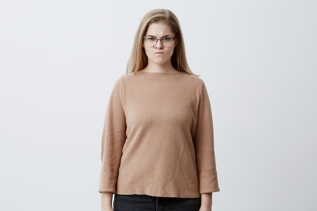 Aggravated blonde female with straight hair, wears spectacles, frowns face in discontent, feels displeasure, being insulted by someone. caucasian young woman with annoyed face expression