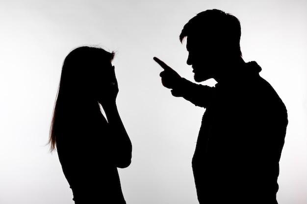 공격성과 학대 개념 - 흰색 배경에 격리된 스튜디오 실루엣에서 가정 폭력을 표현하는 남녀.