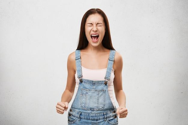 攻撃性、否定的な人間の反応と態度。怒っている屋内のショットは、口を大きく開け、目を閉じ、拳を握り締め、怒り狂った猛烈な表情で若い女性が大声で叫んでいた