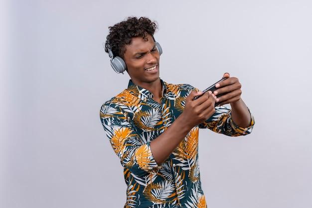 Агрессивный и злой красивый темнокожий мужчина с вьющимися волосами в рубашке с принтом листьев в наушниках играет с мобильным телефоном