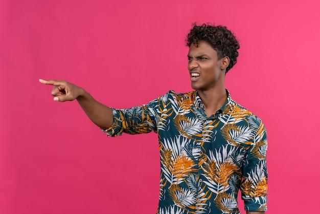 Агрессивный и злой молодой темнокожий мужчина с вьющимися волосами, указывающий указательным пальцем в знак неприязни