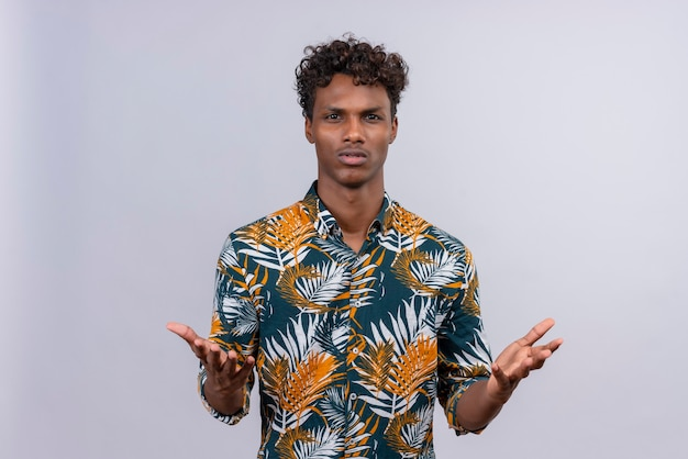 Aggressive and angry dark-skinned man waiting explanationspread hands sideways and staring camera questioned have arguments look bothered and frustrated asking what happened on a white ba
