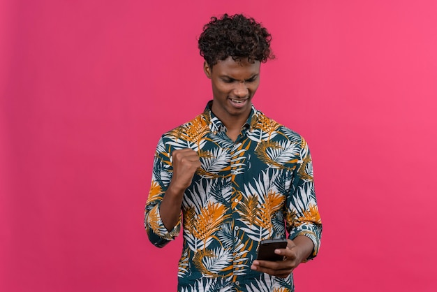 Aggressive and angry dark-skinned man with curly hair in leaves printed shirt losing game on mobile phone with clenching fists