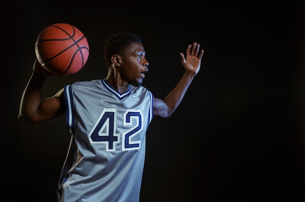 Aggressive basketball player poses with ball in studio, black background. professional male baller in sportswear playing sport game, tall sportsman