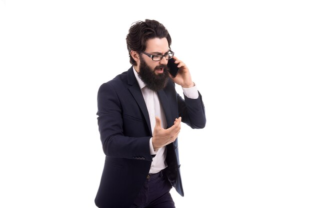 Aggressive bearded businessman swears on the smartphone, isolated on white background