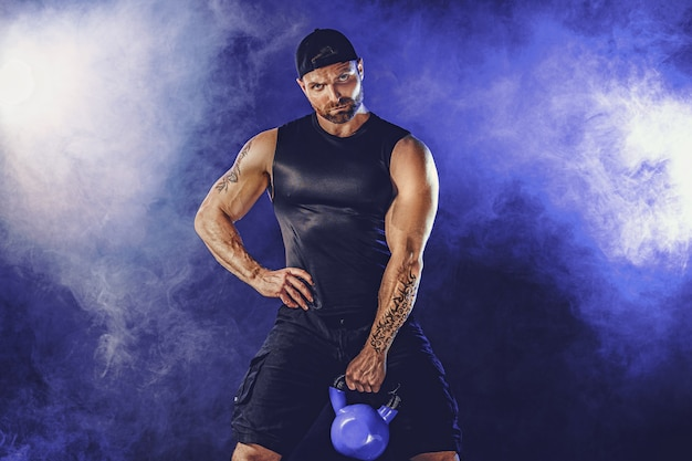 ケトルベルで上腕二頭筋の運動をしている攻撃的なひげを生やした筋肉のボディービルダー。