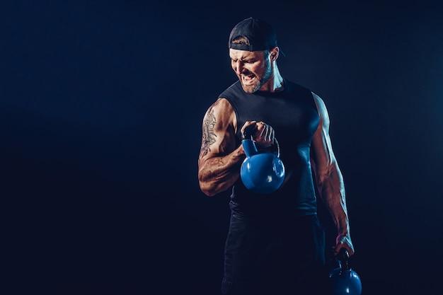 ケトルベルで三角筋、肩の筋肉の運動をしている攻撃的なひげを生やした筋肉のボディービルダー。ショット