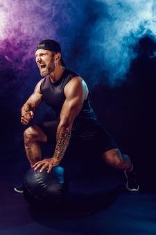 攻撃的なひげを生やした筋肉のスポーツマンが運動している、煙で暗い壁に隔離された薬のボールで押し上げます。