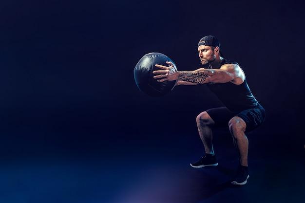 공격적인 수염 근육 스포츠맨은 어두운 벽에 고립 된 의학 공을 가지고 운동하고 있습니다.