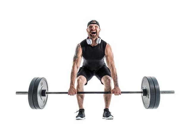 スポーツウェアとヘッドフォンでデッドリフト運動をしている攻撃的なひげを生やした強い筋肉質の男。白地にフルレングス。