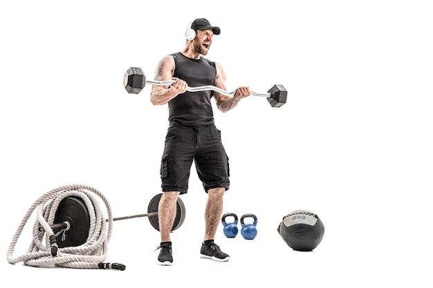 Агрессивный бородатый сильный мускулистый мужчина в спортивной одежде и наушниках с штангой на белом изолировать.