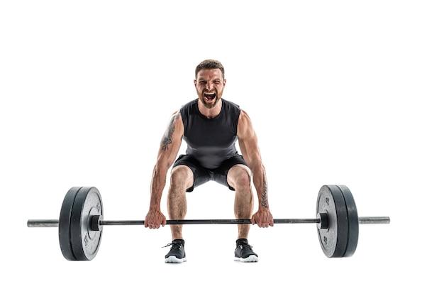 デッドリフト運動をしているスポーツウェアの攻撃的なあごひげを生やした強い筋肉質の男。白地にフルレングス。