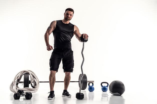 Агрессивный бородатый сильный мускулистый мужчина в спортивной одежде со штангой и спортивным оборудованием на белом изолировать.
