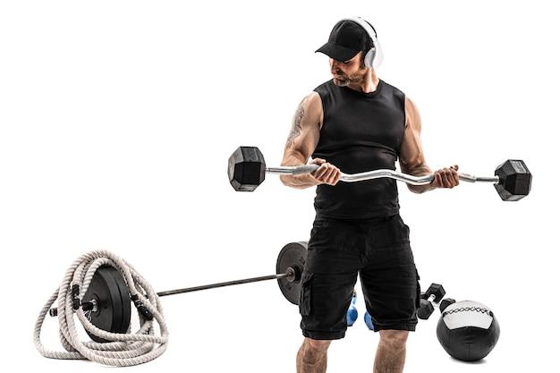 Агрессивный бородатый сильный мускулистый мужчина в спортивной тренировке со штангой на белом изолировать.