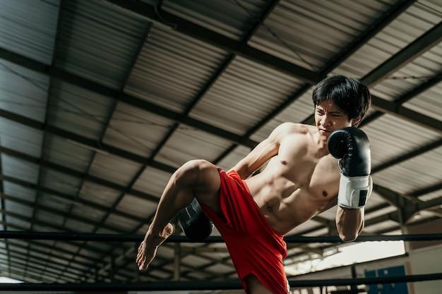 권투 장갑의 공격적인 권투 선수는 권투 훈련 홀에서 권투 링에서 무릎을 걷어차