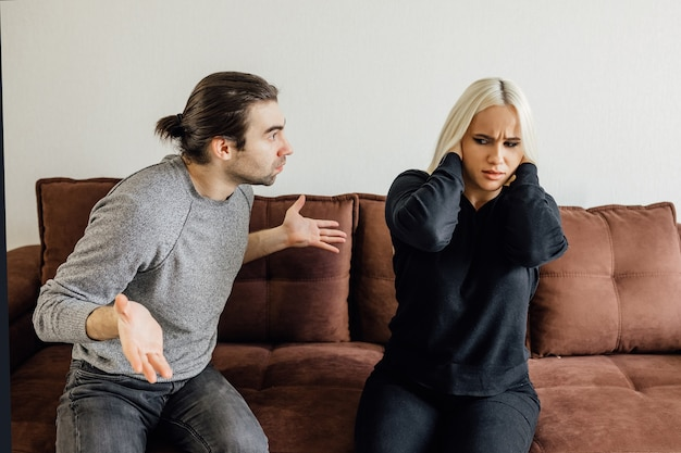 Aggressive boyfriend yelling at sad lady upset girl sitting silent holding head in hands