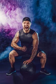 공격적인 잔인한 수염 난 근육 운동가는 연기와 함께 어두운 벽에 고립 된 의학 공을 가지고 운동하고 있습니다.