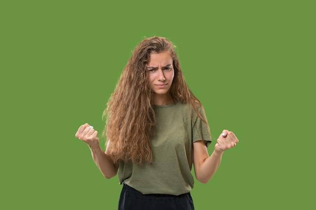 Donna aggressiva di affari che sta isolata sul verde alla moda