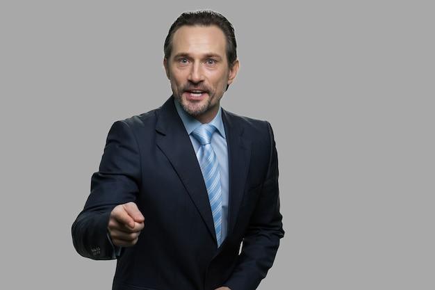 攻撃的なビジネスマンが叫び、カメラを指しています。猛烈な成熟した幹部が叫び、カメラに人差し指で示しています。