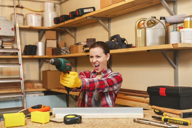 格子縞のシャツと灰色のtシャツを着た積極的な白人の若い茶色の髪の女性は、テーブルの場所で大工のワークショップで働いており、家具を作りながら鉄と木片にドリル穴を開けています。