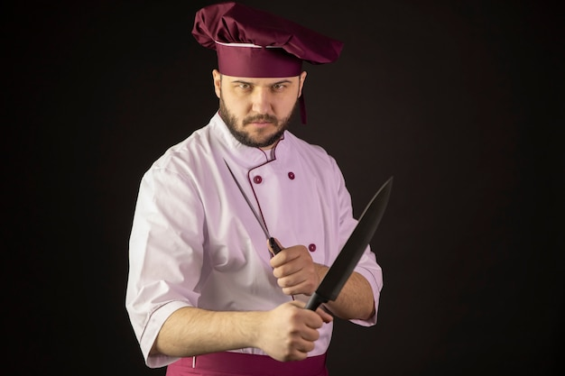 Aggressive chef man in uniform holds two knives crossing them as fighting