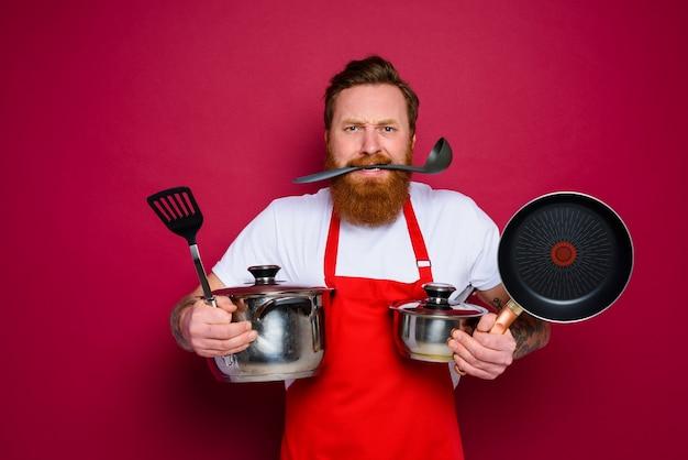 수염과 빨간 앞치마를 가진 공격적인 요리사가 요리 할 준비가되었습니다.