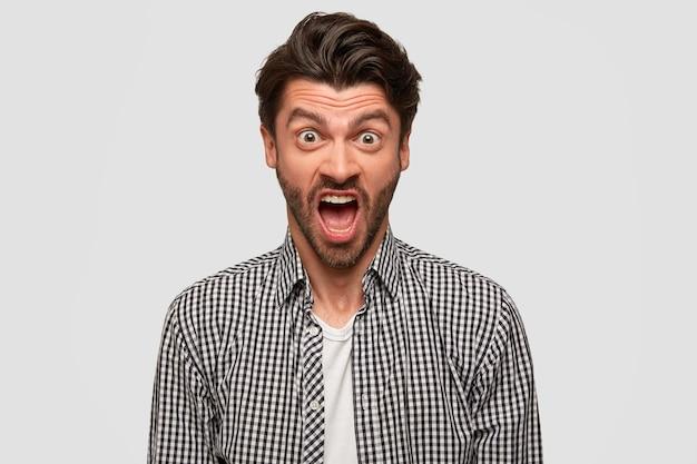 L'uomo barbuto furioso aggressivo ha un'espressione facciale infastidita, alza le sopracciglia, grida a qualcuno durante la lite