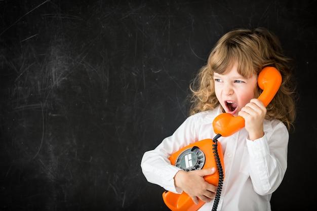 빈티지 전화로 전화하는 공격적인 아이